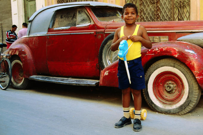 Young boy with hobby horse in front of old car.