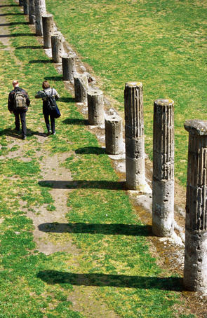 Couple walking past columns in Casermi dei Gladiatori, Old Pompeii.