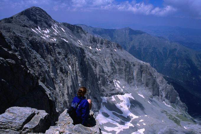 Trekker resting beneath western face of Mytikas on Mt Olympus.