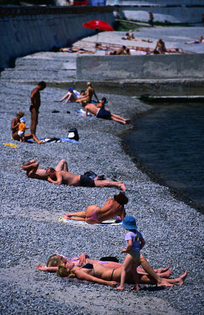 People sunbathing on Arkadia Beach with waters of Black Sea.