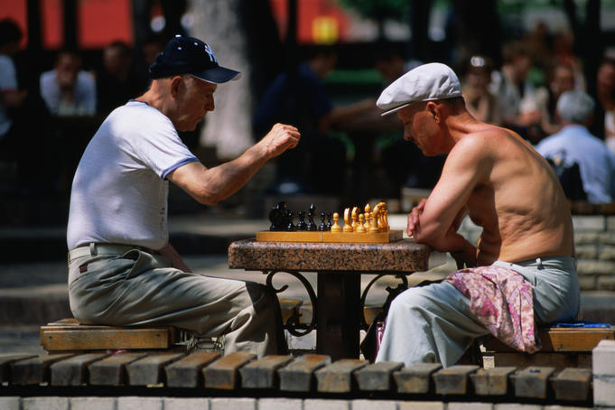 Men playing chess under chestnut trees in Shevchhenko Park.