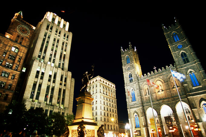 Place d'Armes and Notre-Dame Basilica illuminated at night.
