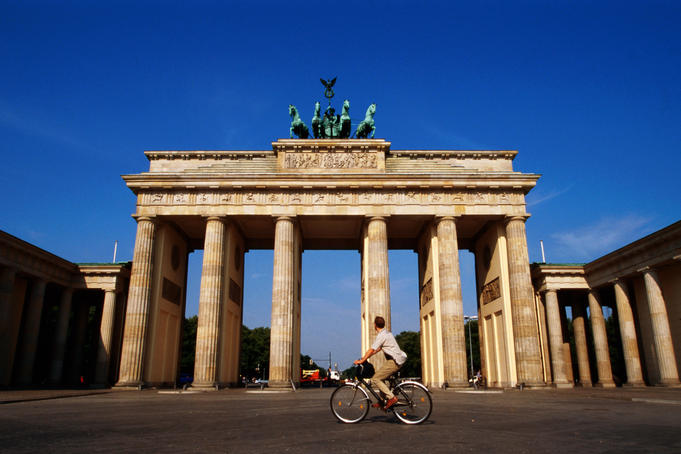 Man cycling past Brandenburger Tor.