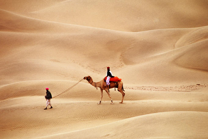 Overhead of Rajasthani men with camel on dunes.