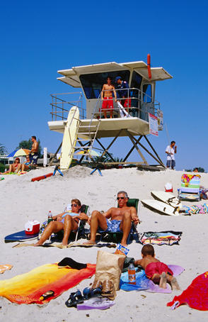 Sunbathers with lifeguard station in background at Moonlight Beach.