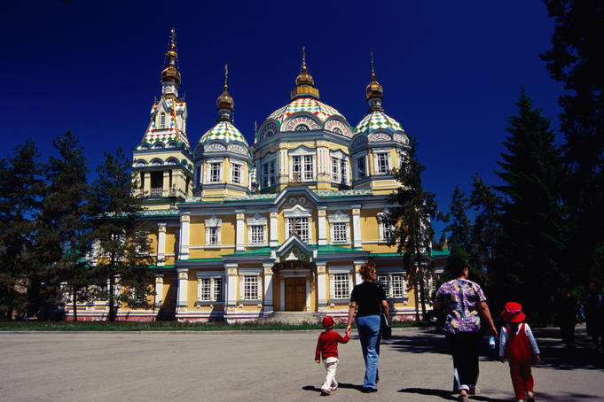 Family walking outside Zenkov Cathedral in Panfilov Park.