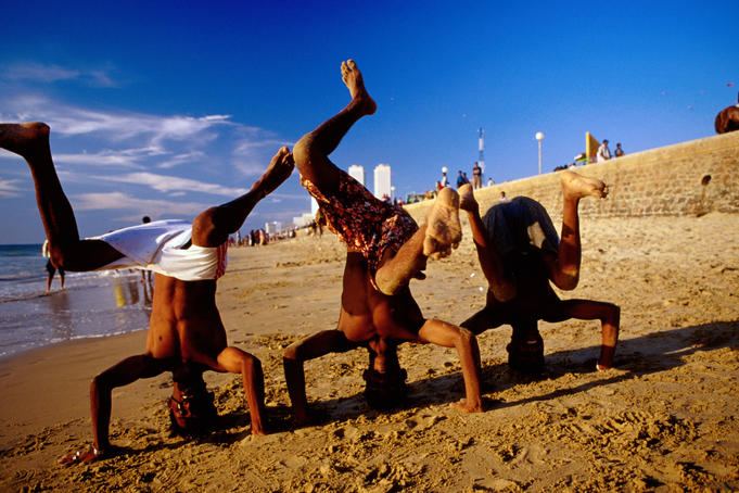 Boy performing handstands on Galle Face Beach.