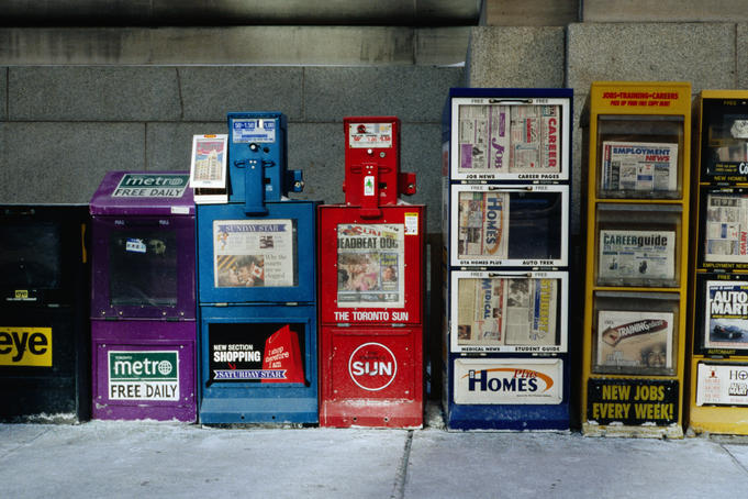 Newspaper boxes lined up on street.