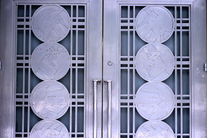 Detail of art-deco door on Design Exchange building, depicting city's historical occupations.
