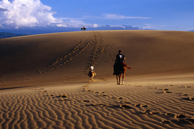 People horse riding in sand dunes.
