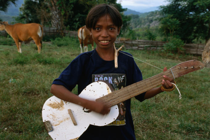 Boy playing home-made guitar in Aidabaleten village.