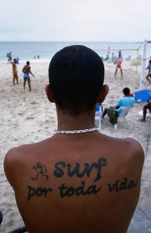 "Boy with tatoo on back that reads ""surf all life long"" on Ipanema beach."