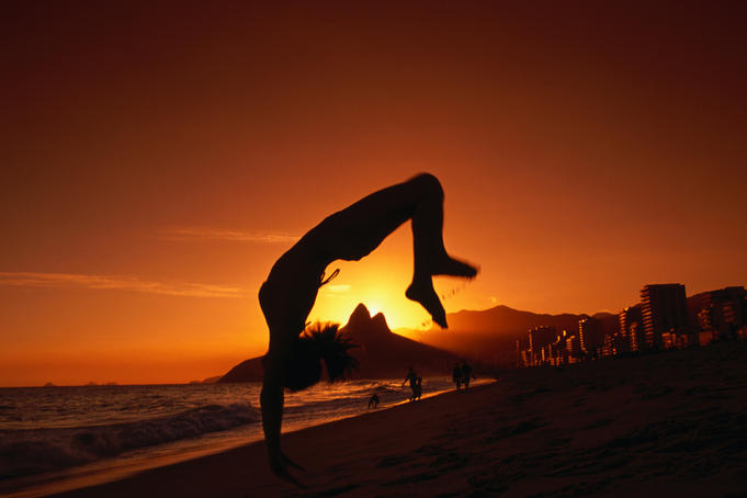 Man doing somersault on beach at sunset.
