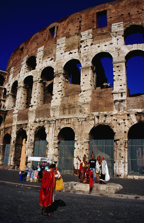 'Gladiators' pose with tourists outside Colosseum.