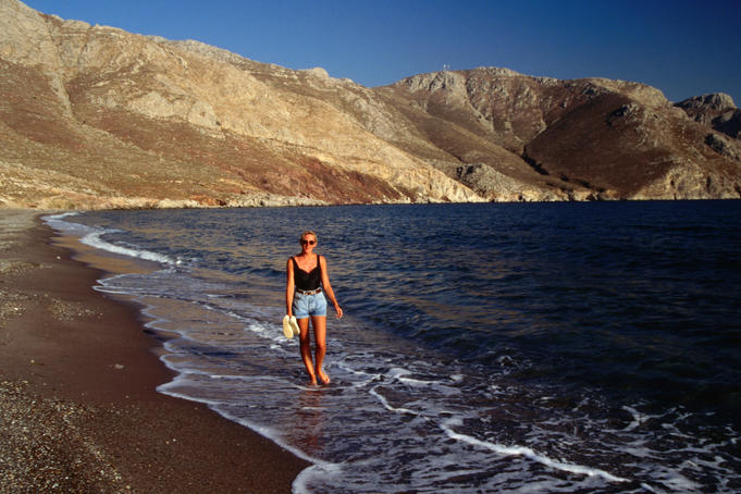 Woman walking along tranquil beach, Tilos.