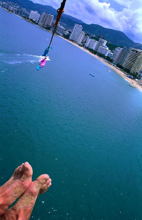 Sandy feet of parasailer and high angle view of city.
