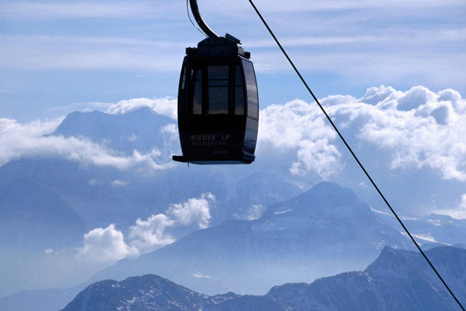 Moosfluh ropeway with peaks and clouds in background.