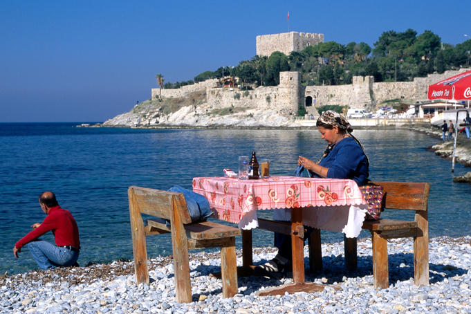 Fisherman's wife knitting on beach in front of the castle (Guvercin Adasi).