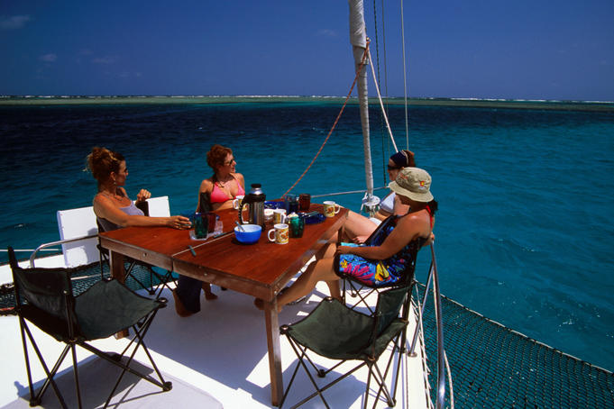 Tourists sitting around table on deck of sailing vessel.