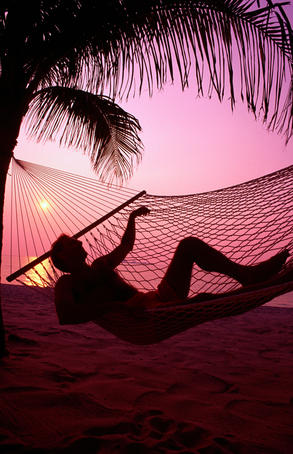 Man relaxing in hammock on beach at sunset.