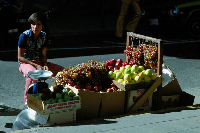 A fruit vendor offering grapes, apples and pears on the streets of San Jose