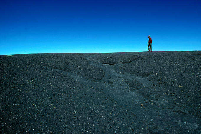 Man walking on rim of Irazu volcano crater, against blue sky.