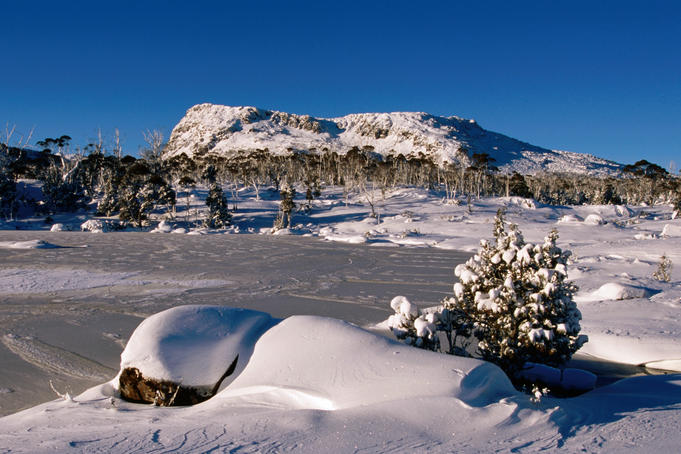 Frozen tarn and King Davids peak under winter snow.