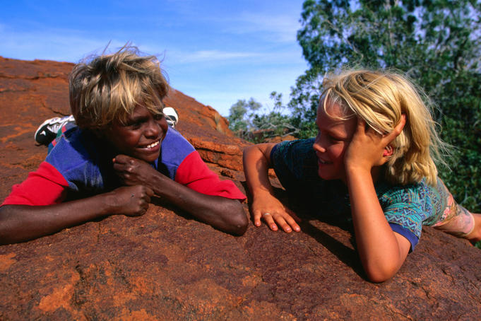 Children talking on a rock in the Western Desert.