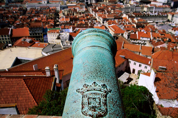 Overhead of city with cannon of Castelo de Sao Jorge in foreground.