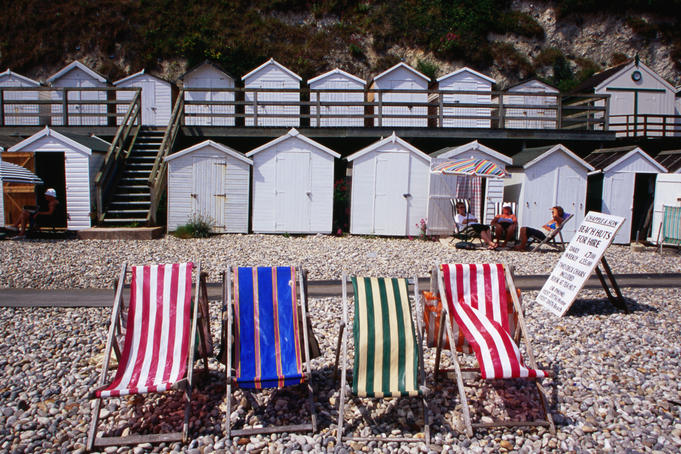 Striped deckchairs and bathing huts on pebbled Beer beach.
