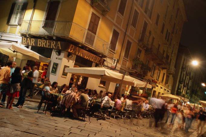 People at outdoor tables of Bar Brera in Brera district at night.
