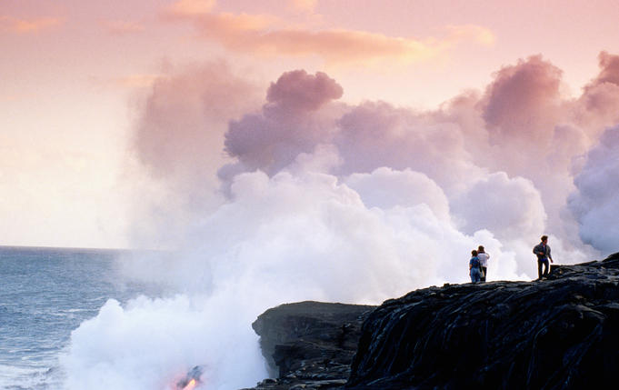 People watching lava flow into ocean.