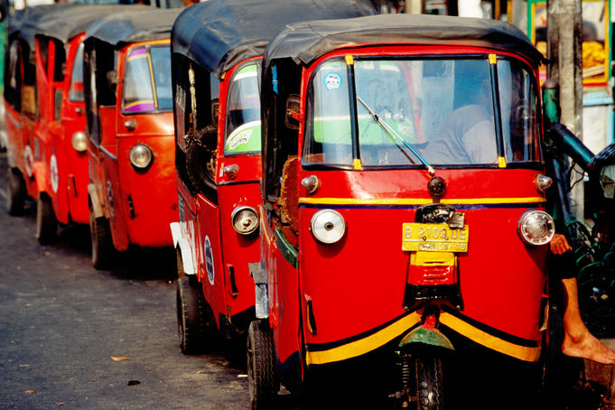 Three-wheeled Bajaj transportation lined up in street.