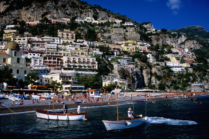 Houses terraced into rugged Amalfi coastline, boats in foreground.
