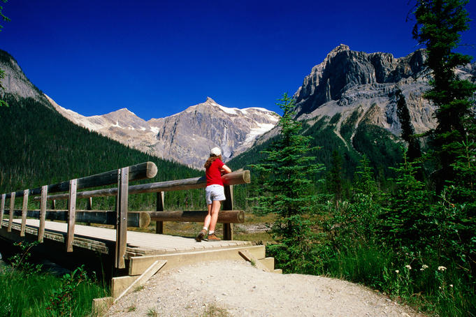 Hiker on bridge near Emerald Lake with mountain backdrop.