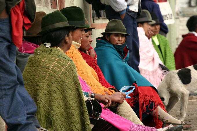 Women sitting in colourful ponchos and hats.