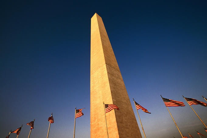 American flags flying at base of Washington Monument.