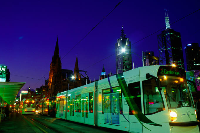 Tram stops for passengers in city at night.