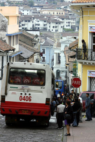Large bus in narrow street.