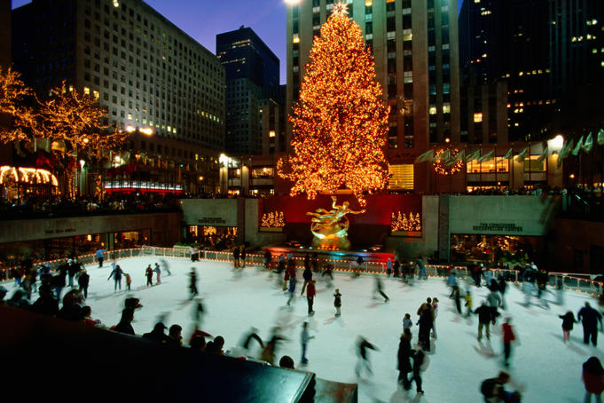 Skaters on rink at Rockefeller Center underneath Christmas tree and statue of Prometheus, Manhattan.