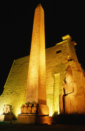 Luxor Temple at night: the light show creates an eerie spectacle as the temple is lit up and the statues and Obelisk are featured - Luxor