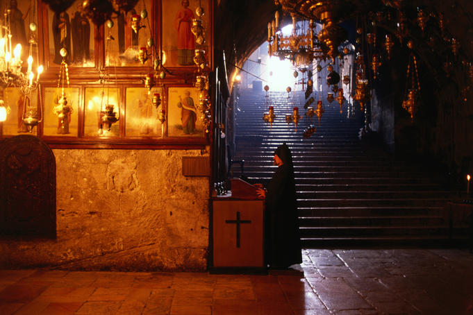 Priest in Greek Orthodox Church of St John surrounded by many censers.