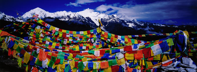 Buddhist prayer flags with Meili Xueshan mountain range in background.