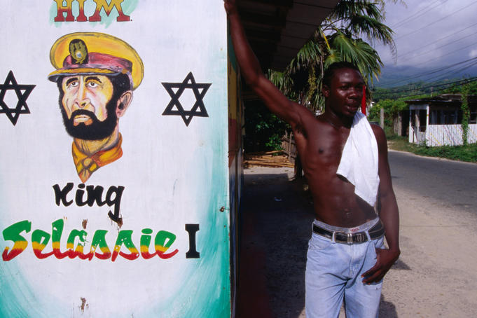 Man standing next to mural of King Selassie I.