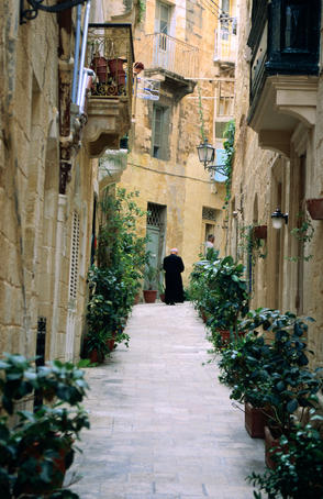 A priest walks a narrow laneway in historic Vittoriosa.