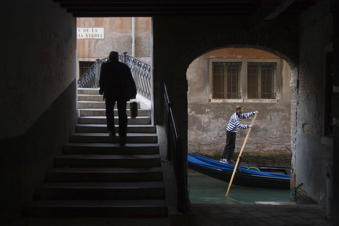 Man walking near gondola, classic Venician scene.