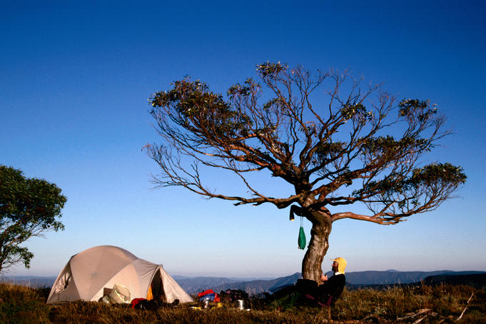 Bushwalker and tent on summit of Mt Speculation .