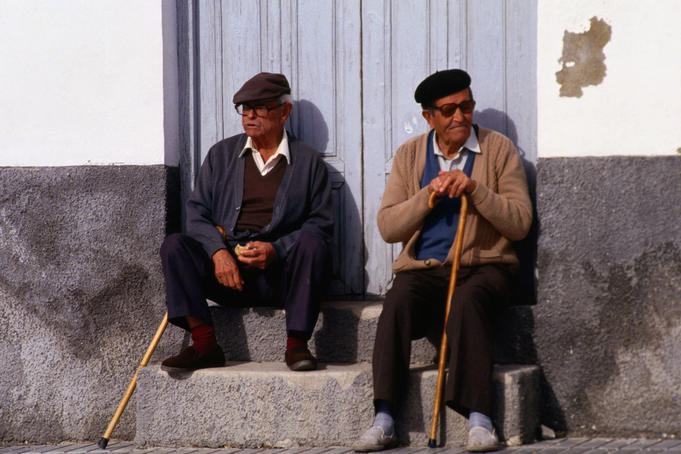 Elderly men with walking sticks sitting in street.