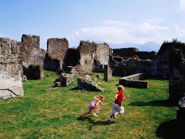 Boy and girl playing among Roman ruins.