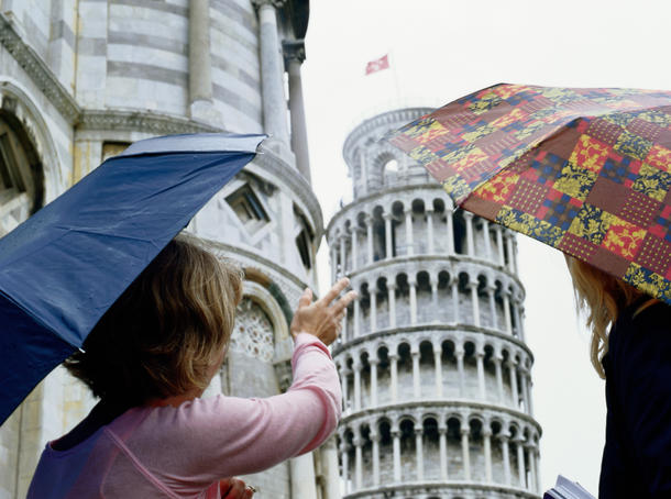 Women with umbrellas looking at Leaning Tower of Pisa.